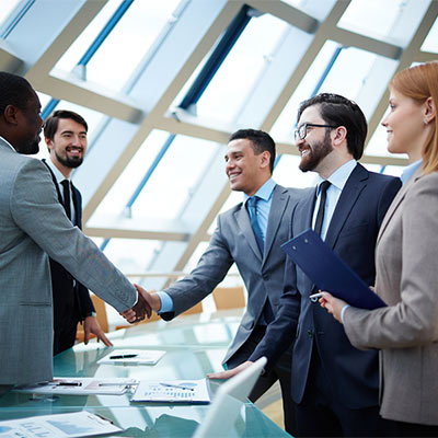 People at a desk shaking hands while buying a business at closing